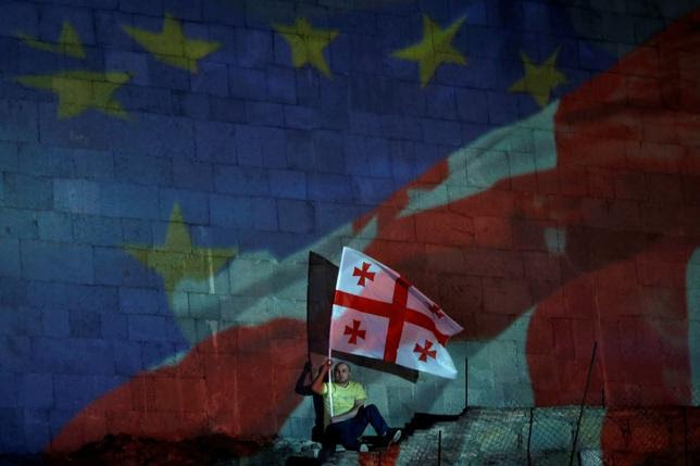 A man with a Georgian flag sits in front of a projection of the Georgian and European flags during celebrations for the signing of an association agreement with the EU in Tbilisi, June 27, 2014.  REUTERS/David Mdzinarishvili
