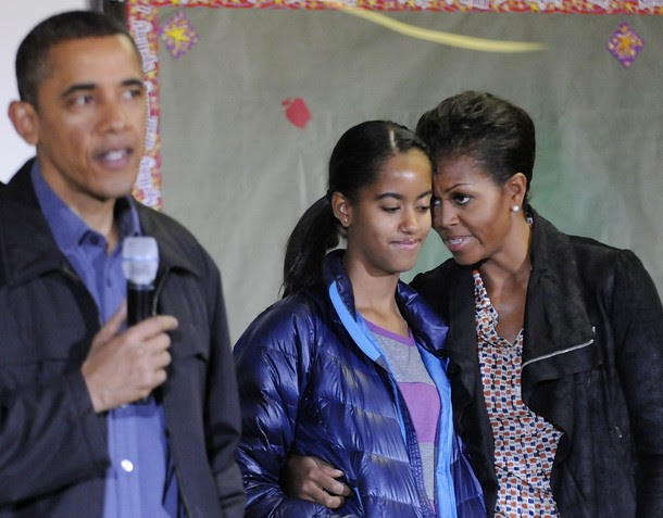 Michelle Obama stands with her daughter Malia as Obama delivers remarks during a day of service to honor Martin Luther King, Jr, at a school in Washington