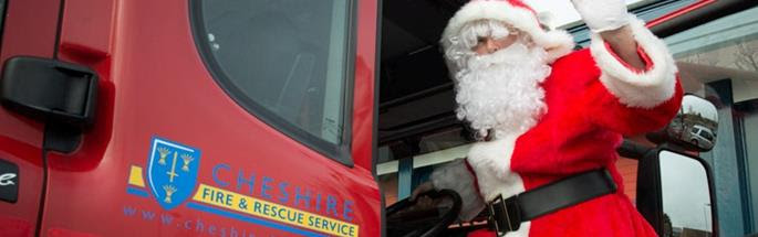 Santa climbing into a fire engine