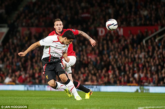 In the action: Suarez gets a header in as United left back Alex Buttner watches on