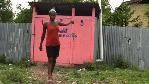 Woman at Leogane camp saying the latrines behind her are full and smell foul. / Credit:Haiti Grassroots Watch