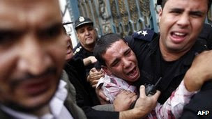 An opposition protester is helped by police in Cairo (5 Dec 2012)