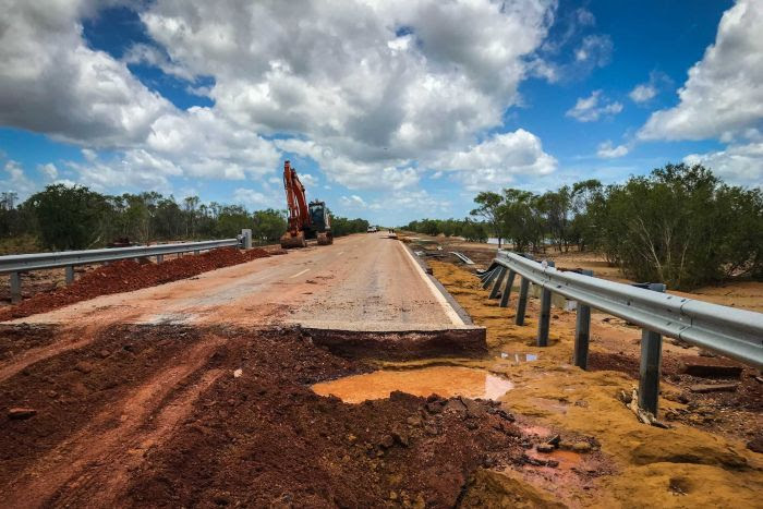 A bitumen road destroyed by flooding, with red dirt in the foreground, and a digger further down the road.