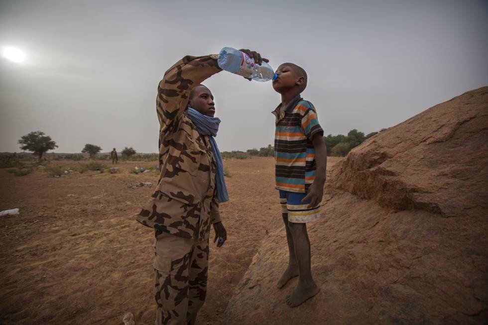 Un miembro del contingente chadiano de la Misión Integrada de Estabilización de las Naciones Unidas en Malí ofrece a un niño un trago de agua. Diciembre 2016.