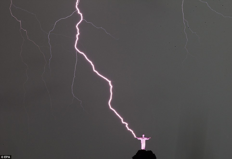 View of lightning striking Christ the Redeemer in Rio de Janeiro, Brazil, 16 January 2014. The city suffered a strong storm that left neighborhoods without power and flooded streets