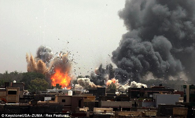 Smashed: Smoke rises from explosions as Nato airstrikes hit Tripoli. The alliance is stepping up their air campaign in the country