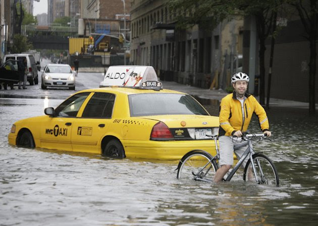 A bicyclist makes his way past a stranded taxi on a flooded New York City Street as Tropical Storm Irene passes through the city, Sunday, Aug. 28, 2011. Although downgraded from a hurricane to a tropi