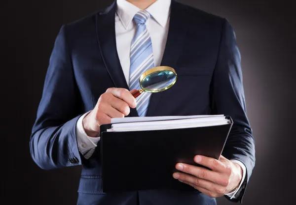 Empresario examinando documentos con lupa — Foto de Stock #46203147