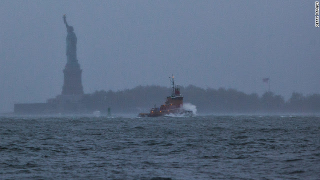 A wave crashes over the bow of a tugboat in New York Harbor on Monday.