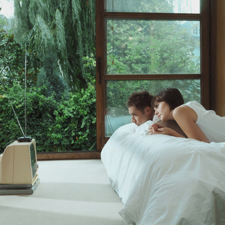 people with a tv in their bedroom have more sex - couple watching tv in bed - evening bag - handbag
