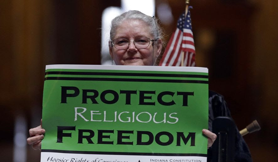 Condy Holmes of Mechanicsburg, Ind. holds a sign a rally at the Statehouse in Indianapolis, Monday, April 27, 2015 against the revised religious freedom legislation. The group of conservative religious leaders is rebuking Gov. Mike Pence and the leaders of the Republican-dominated General Assembly for changes to Indiana's religious objections law that they claim threaten religious liberties.(AP Photo/Michael Conroy)