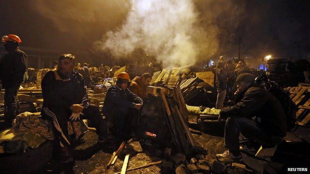 Anti-government protesters rest next to a barricade in the Independence Square in Kiev on 21 February 2014.