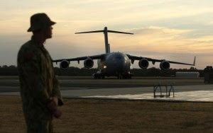 An Australian Air Force serviceman watches as an Australian Air Force C-17 taxis on the tarmac of the RAAF Base Pearce near Perth