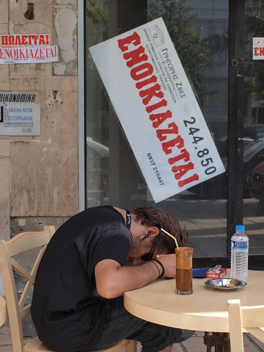 For Rent says the sign behind the man. Thessaloniki, Greece