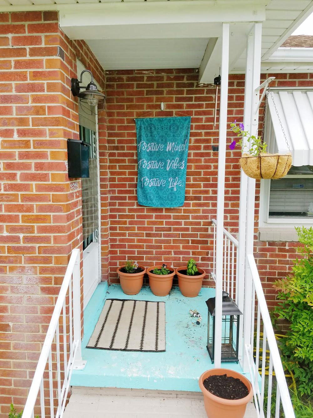 Aqua front porch. Bright paint with brick home. Lifestyle boho porch flag @adesignerathome