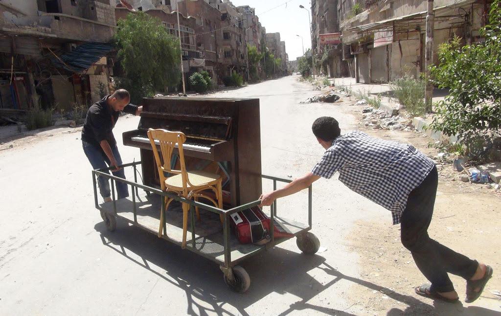 Aeham Ahmad e un suo amico siriano trasportano il pianoforte all'interno del campo palestinese di Yarmouk, il 26 giugno 2014.  - Rami Al Sayed, Afp