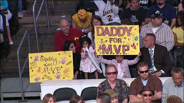 At STAPLES Center, Kobe Bryant's wife and one of their two daughters hold up 'Daddy For MVP' signs during the Lakers' game against the San Antonio Spurs on Sunday.