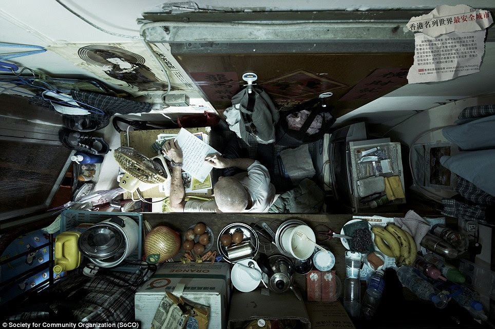 No room to swing a cat: An elderly gentleman writes a letter completely surrounded by his life's possessions. It's not clear from the angle of this image where he sleeps or how he gets in and out