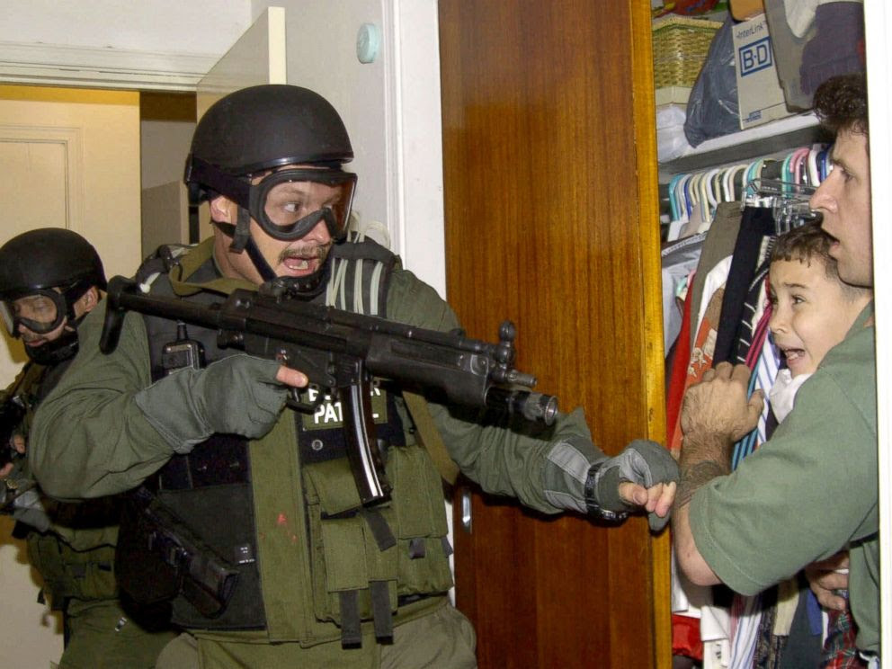 PHOTO: Elian Gonzalez is held in a closet by Donato Dalrymple, one of the two men who rescued the boy from the ocean, right, as government officials search the home of Lazaro Gonzalez for the young boy, April 22, 2000, in Miami.