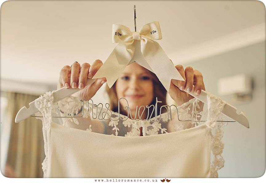 Cool shot of bride holding wedding dress - www.helloromance.co.uk