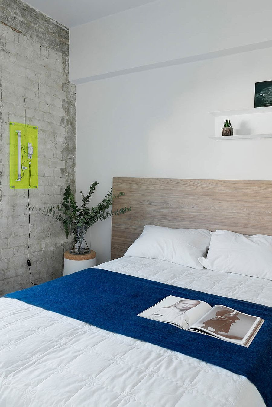 Whitewashed brick wall inside small, contemporary bedroom