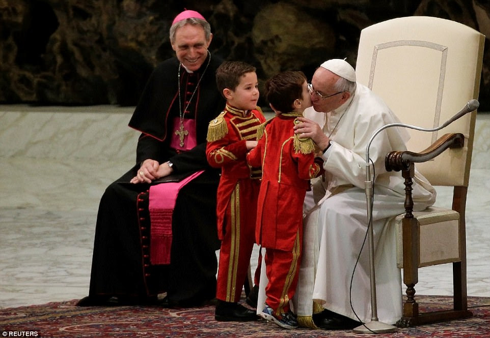 Young admirers: Pope Francis kisses two children dressed as ringmasters who took part in the circus performance in Paul VI hall at the Vatican