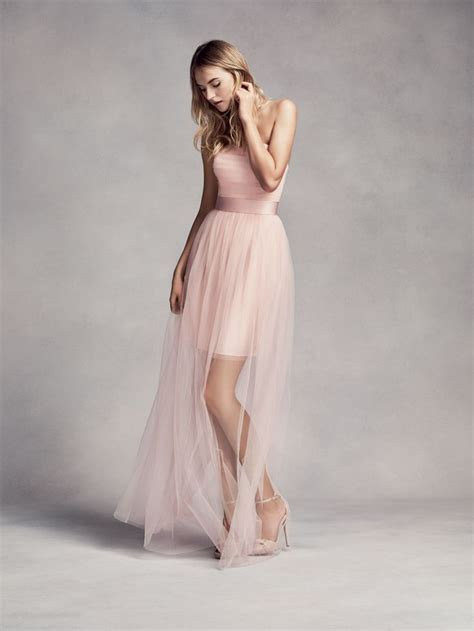 A blush pink bridesmaid dress with a long sheer overlay by