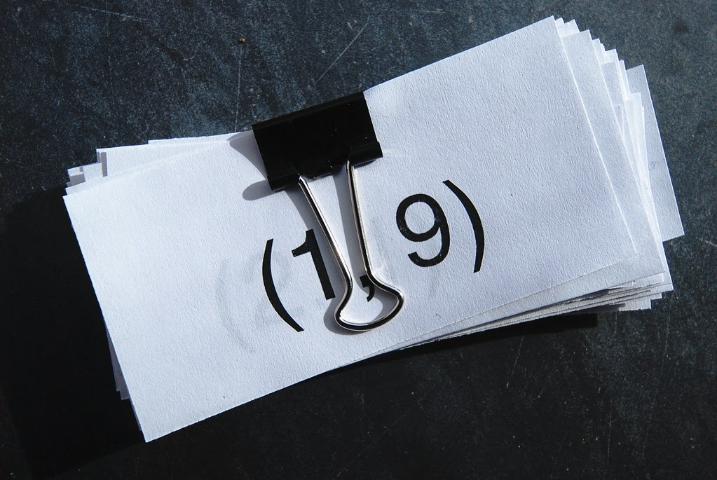 A clipped pile of papers with numbers on them.