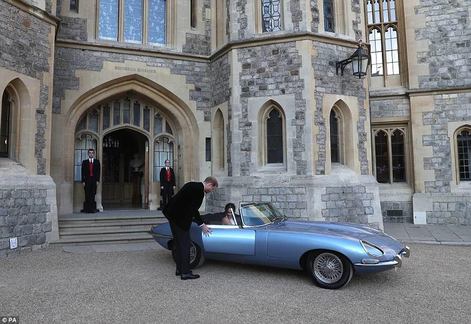Harry ayuda a su nueva esposa Meghan a salir del convertible Jaguar mientras se dirigen a Frogmore House para la recepción