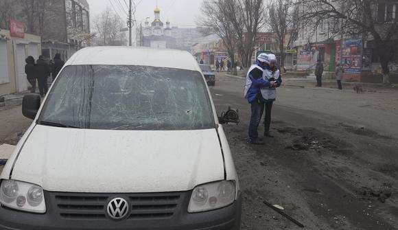 Os membros da Organização para a Segurança e Cooperação na Europa (OSCE) veja os restos de um shell em uma rua depois de um bombardeio por rebeldes pró-russas de um setor residencial em Mariupol, leste da Ucrânia, 24 de janeiro de 2015. REUTERS / Nikolai Ryabchenko