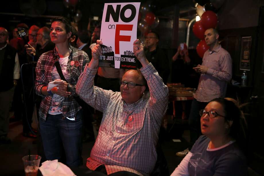 "Bruce Bennett holds a ""No on F"" sign during an election night party at Oasis in San Francisco, California, on Tuesday, Nov. 3, 2015. Photo: Connor Radnovich, The Chronicle"