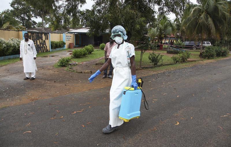 Enfermeira passa desinfetante nas imediações de hospital usado para tratar pacientes com ebola, na Libéria (Foto: EFE)