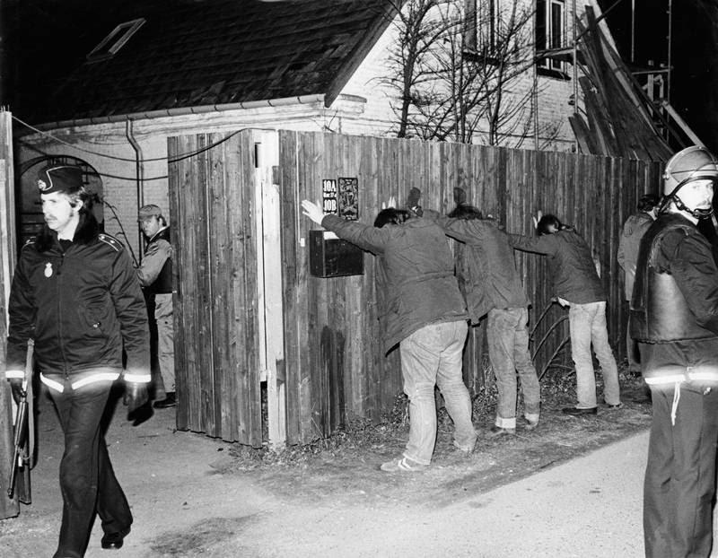 Medlemmer af Black Sheep stillet op ad plankeværket ved Fort Snoldelev under en ransagning efter drabet på Kenneth Melby i 1983. (Foto: Heine Petersen)