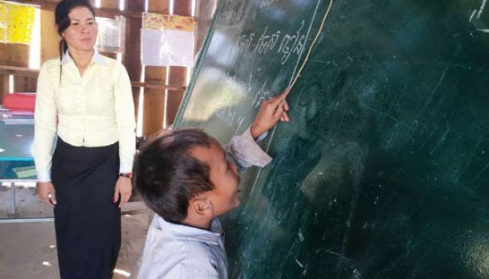 A student at a blackboard receives instruction from his teacher in Kratie province earlier this year. Photo supplied