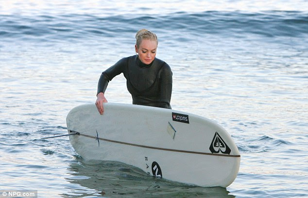 Hang ten: The actress struggled with a big surf board as she left the water
