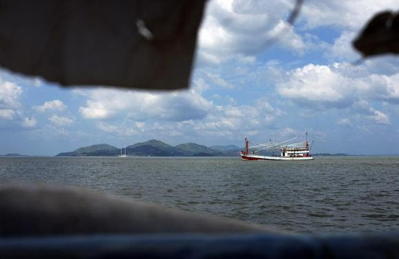 A Thai fishing boat plies the invisible maritime border between Thailand and Myanmar, with the hills of Myanmar visible in the background November 1, 2013. REUTERS/Andrew RC Marshall