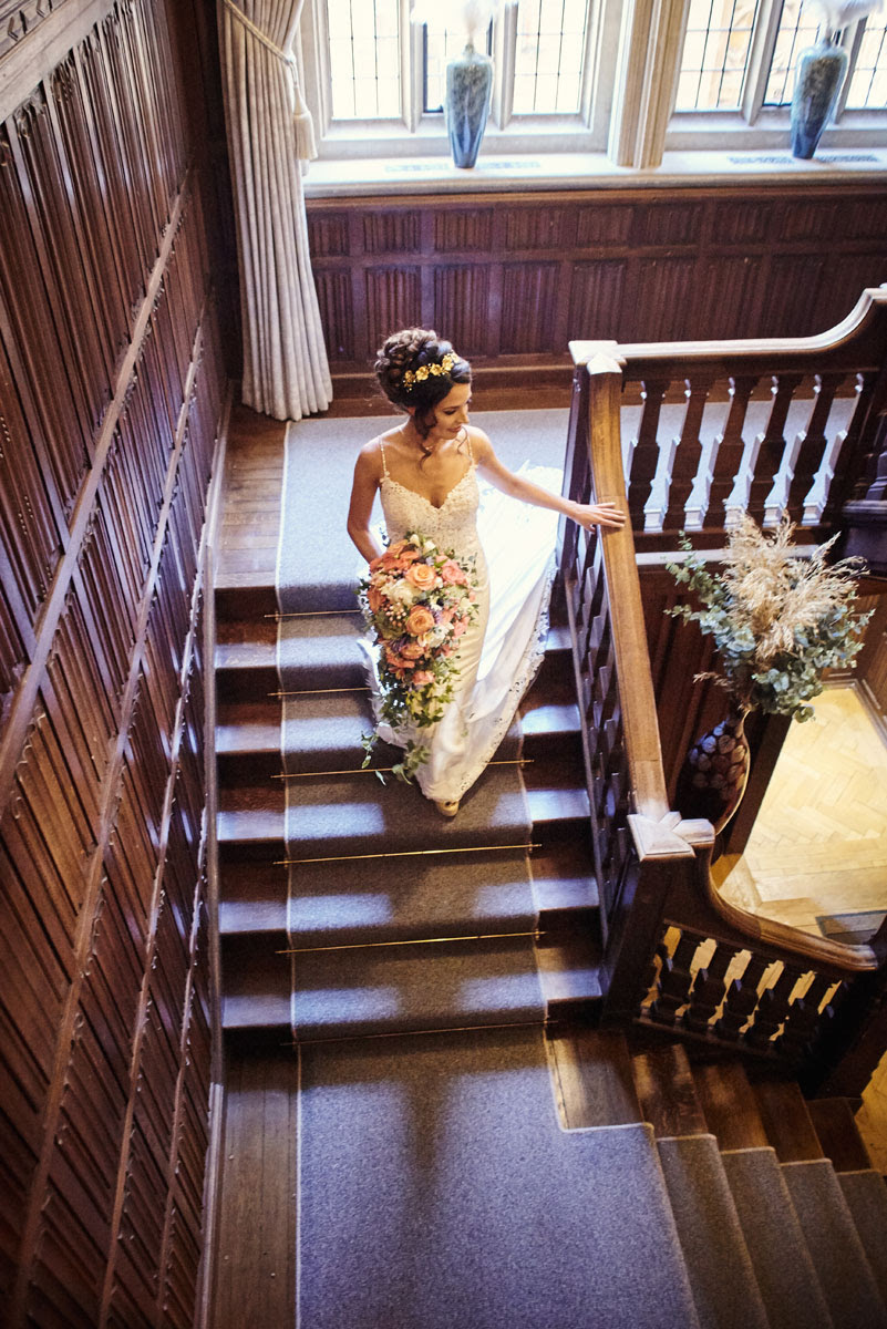 Bride descending ornate wooden staircase at Lanwades Hall Wedding Photos - helloromancephotography.com
