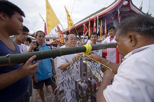 Tying lanterns to the Go Teng pole