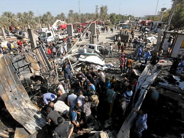 Moradores se reúnem no local do atentado na cidade de Hilla, no Iraque,  neste domingo (6) (Foto: Reuters/Alaa Al-Marjani)