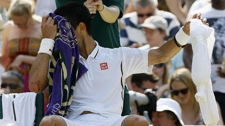Novak Djokovic cools down during a break