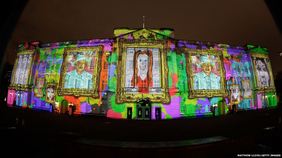Self portraits by children projected onto Buckingham Palace