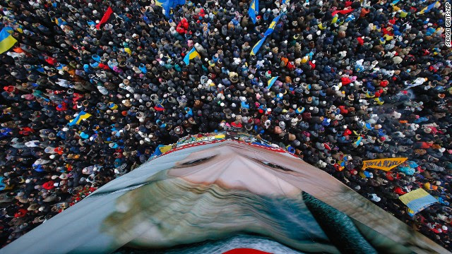 Pro-European Union activists gather around a huge poster of jailed former Ukrainian Prime Minister Yulia Tymoshenko on December 8.