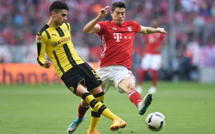 Dortmund's Spanish defender Marc Bartra (L) and Bayern Munich's Polish forward Robert Lewandowski vie for the ball during the German first division Bundesliga football match FC Bayern Munich v BVB Borussia Dortmund in Munich, southern Germany, on April 8, 2017