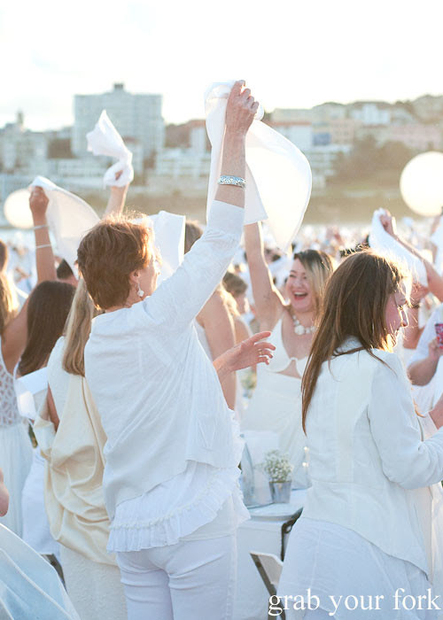Waving of white napkins to signal the start of dinner at Diner en Blanc Sydney 2013 Bondi Beach