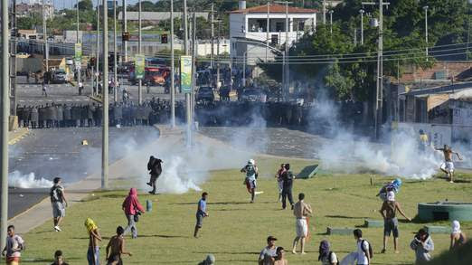Demonstrators run during clashes with riot police near the Estadio Castelao in Fortaleza