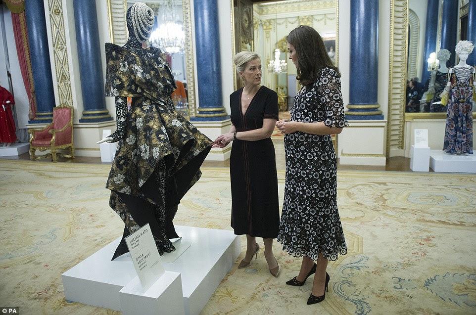 A dupla para admirar um vestido flamboyante floral pela designer canadense Lucian Matis, exibida no Palácio de Buckingham