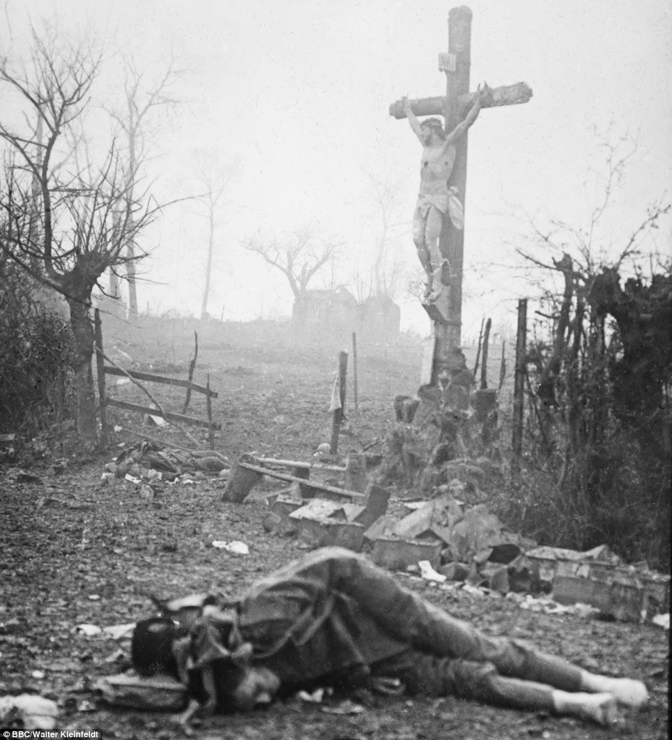 Carnage: Amid the appalling devastation and bodies of dead soldiers, a crucifix stands tall - miraculously preserved from the shell fire. The powerful image was captured after a bloody skirmish in 1917 - and Walter's son Volkmar says: 'This photograph is like an accusation - an accusation against war'