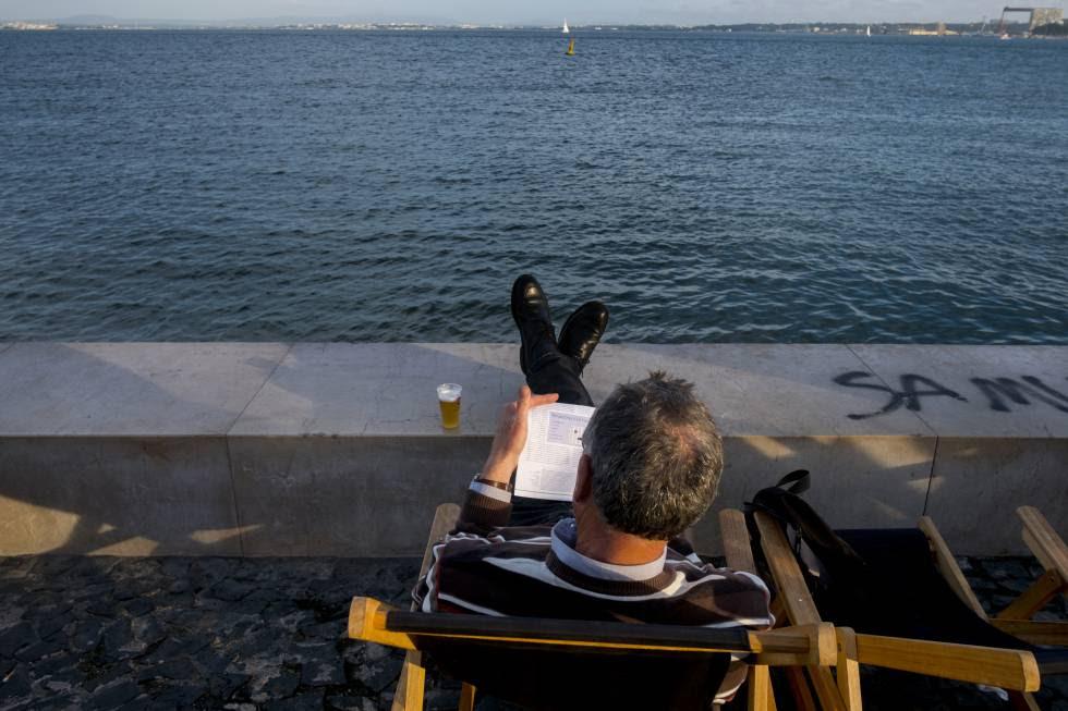 Un hombre lee en la Ribeira das Naus, al lado del río Tajo.