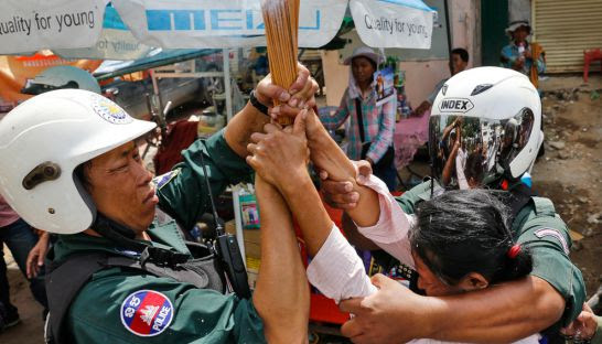 Police hold a woman while breaking up a prayer ceremony held by Borei Keila residents in Phnom Penh yesterday.