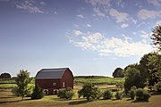 A pastoral farm scene with a classic red barn located in Northern Michigan.